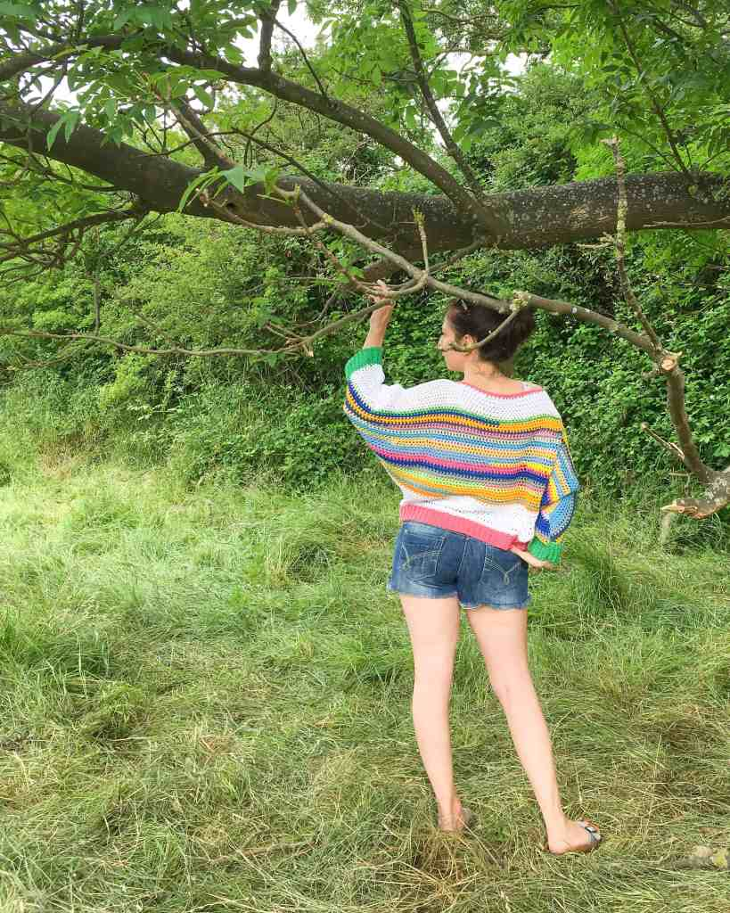 Woman standing in field holding tree wearing rainbow striped crochet batwing sweater with back to camera