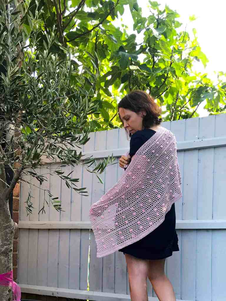 Woman standing in front of blue fence amid trees wearing pink and green crochet wrap