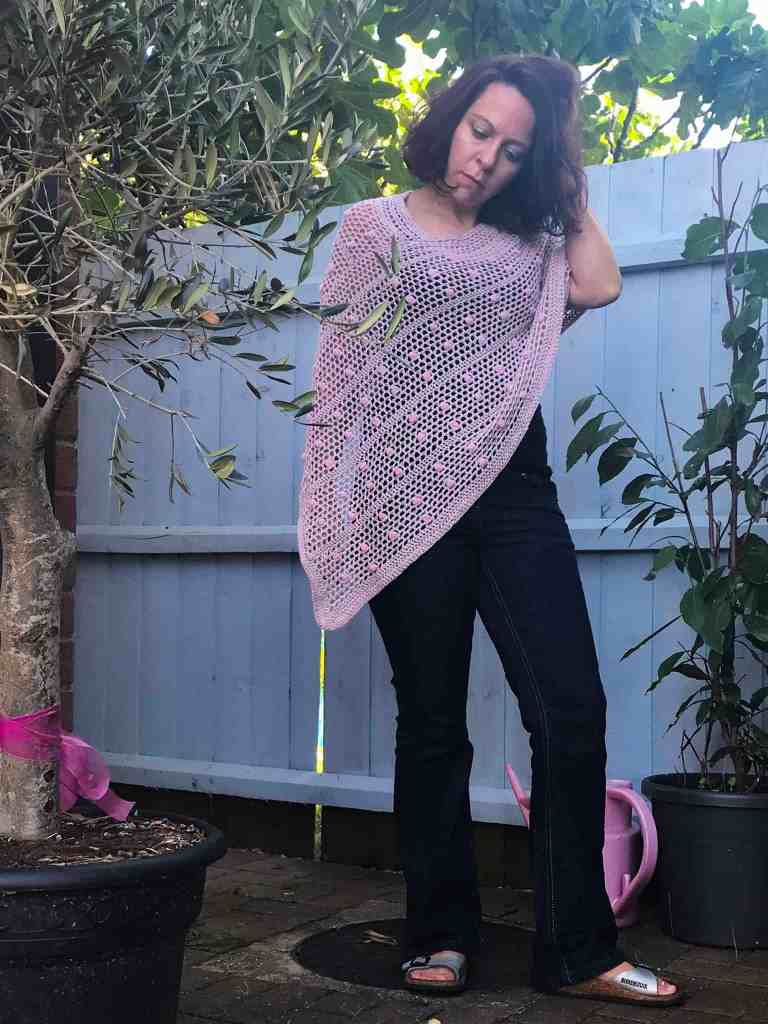 Woman standing in front of blue fence amid trees wearing pink and green crochet poncho