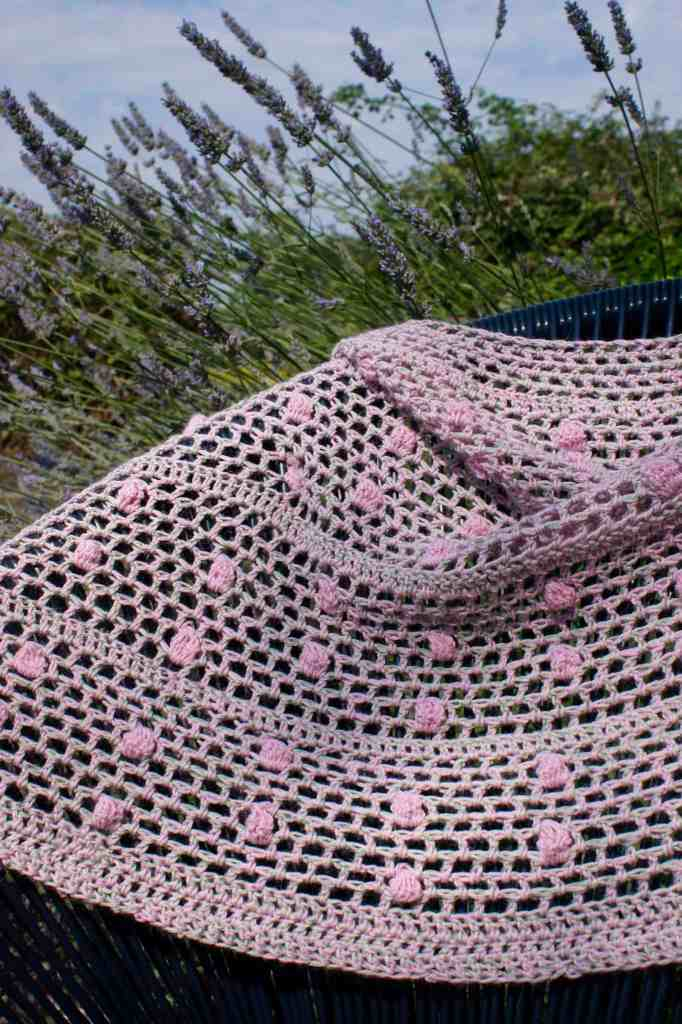 Pink and green crochet poncho draped over chair in front of lavender bush