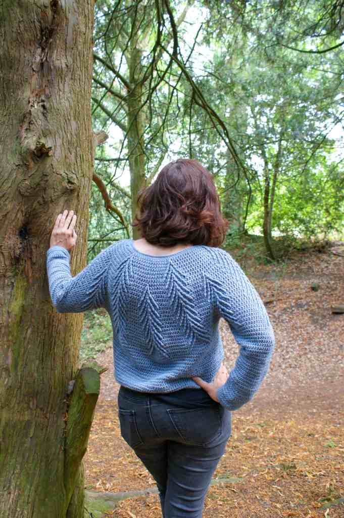 A woman wearing the southern pines blue cabled crochet sweater standing in a wood, with her back to camera, leaning on a tree