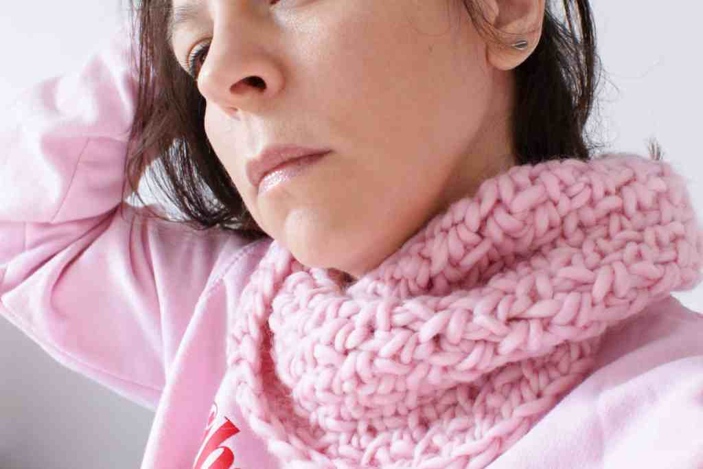 Woman holds hair back whilst wearing pink crochet cowl