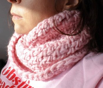 Close up of woman in half shadow with half face hidden wearing pink sweater and crochet cowl
