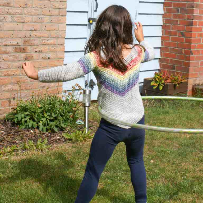Girl playing with a hula hoop wearing crochet rainbow sweater