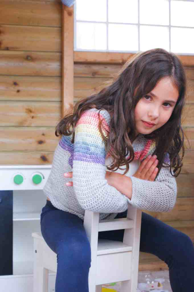 Girl wearing crochet rainbow chevron sweater sat on chair in playhouse