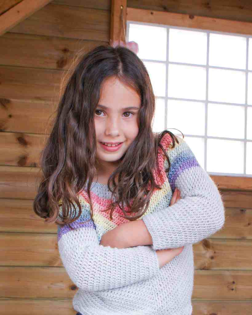 Girl wearing crochet rainbow chevron sweater in playhouse