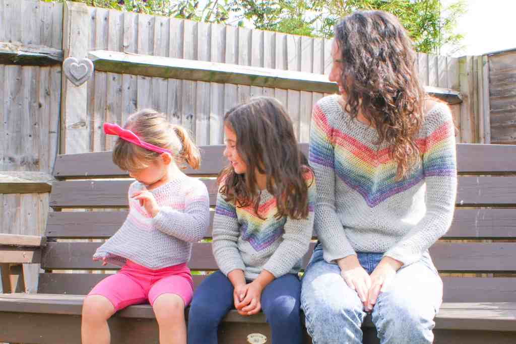Mum and two daughters wearing crochet rainbow sweaters sitting on a bench