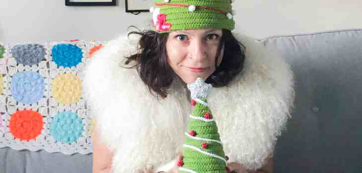 A woman with a cat on her lap both wearing crochet christmas tree hats
