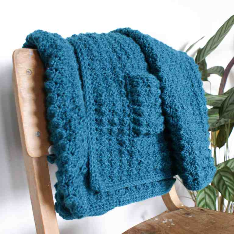 teal crochet cardigan hanging over a wooden school chair