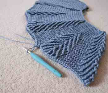 The beginning of a crochet sweater made in the round laying on a beige carpet with turquoise crochet hook