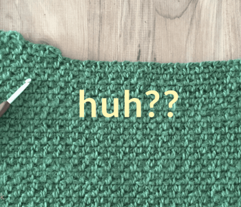 The word huh?? Is written over the two of green crochet fabric on brown wood table