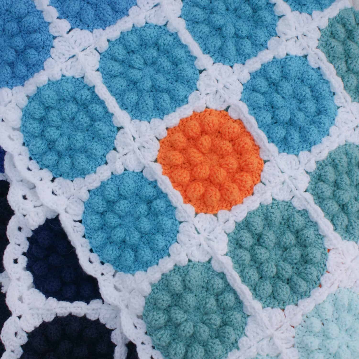 Bobble pop crochet blanket made from blue and orange bobbly circles on white boarder