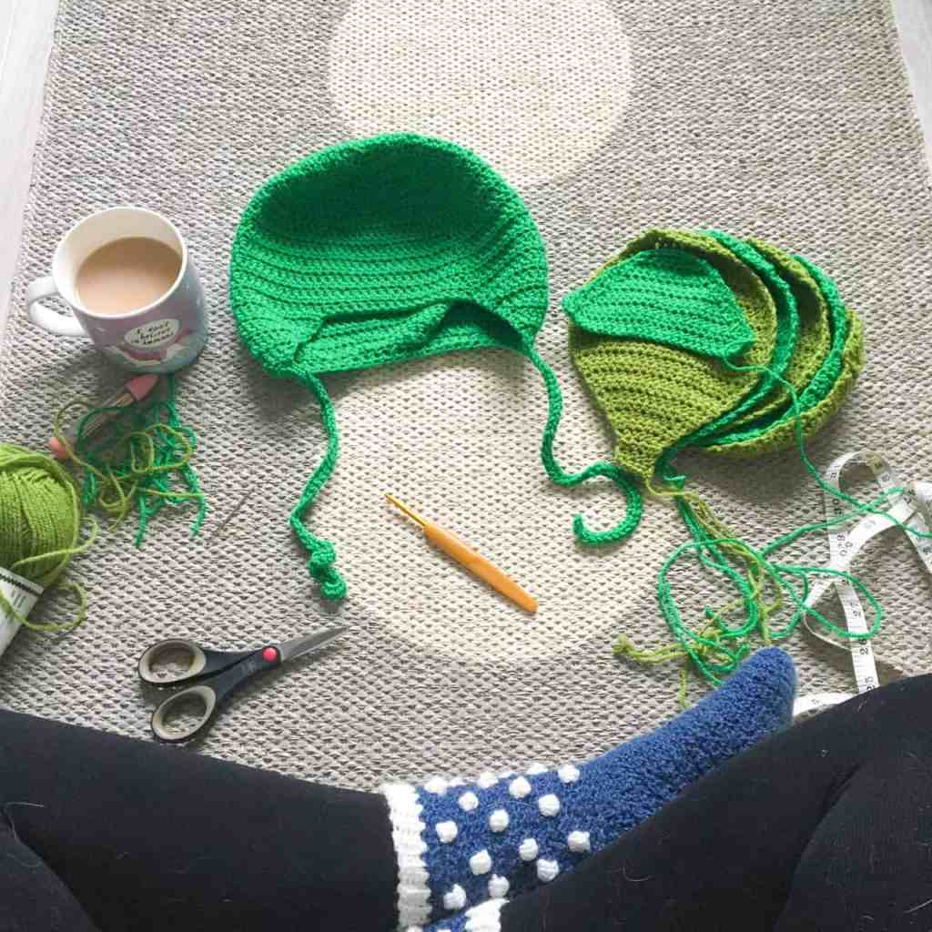 Parts of a crochet Brussel sprout hat and leaves laid out on rug with cup of tea