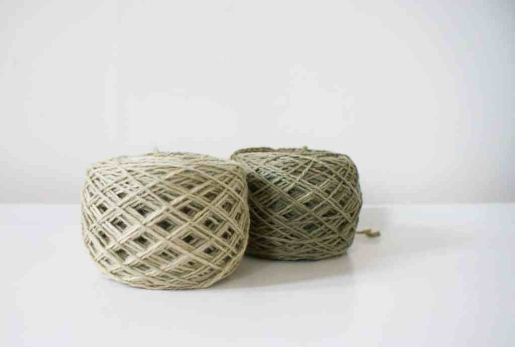 Khaki green yarn cakes hand dyed with nettles on white surface