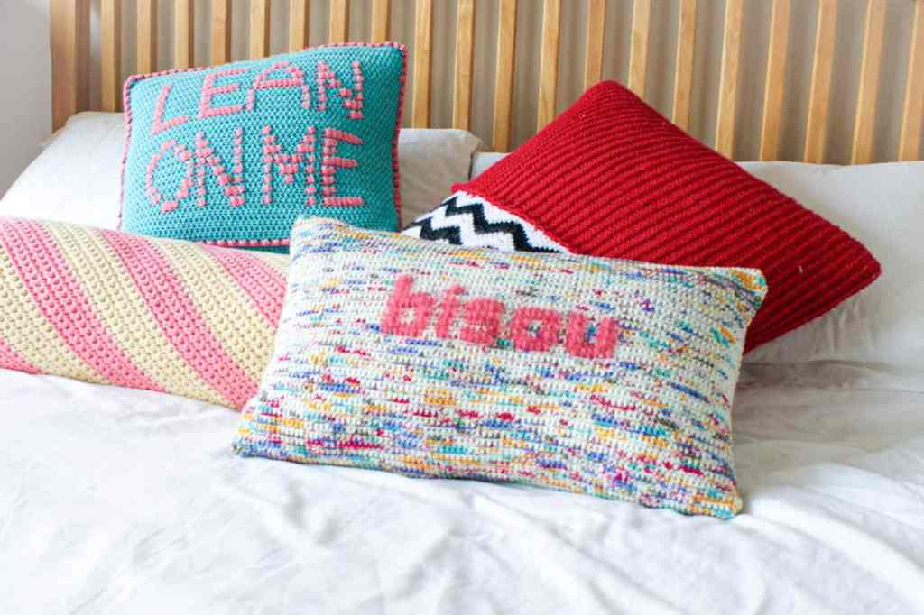 4 brightly coloured crochet cushions on a bed with white linen