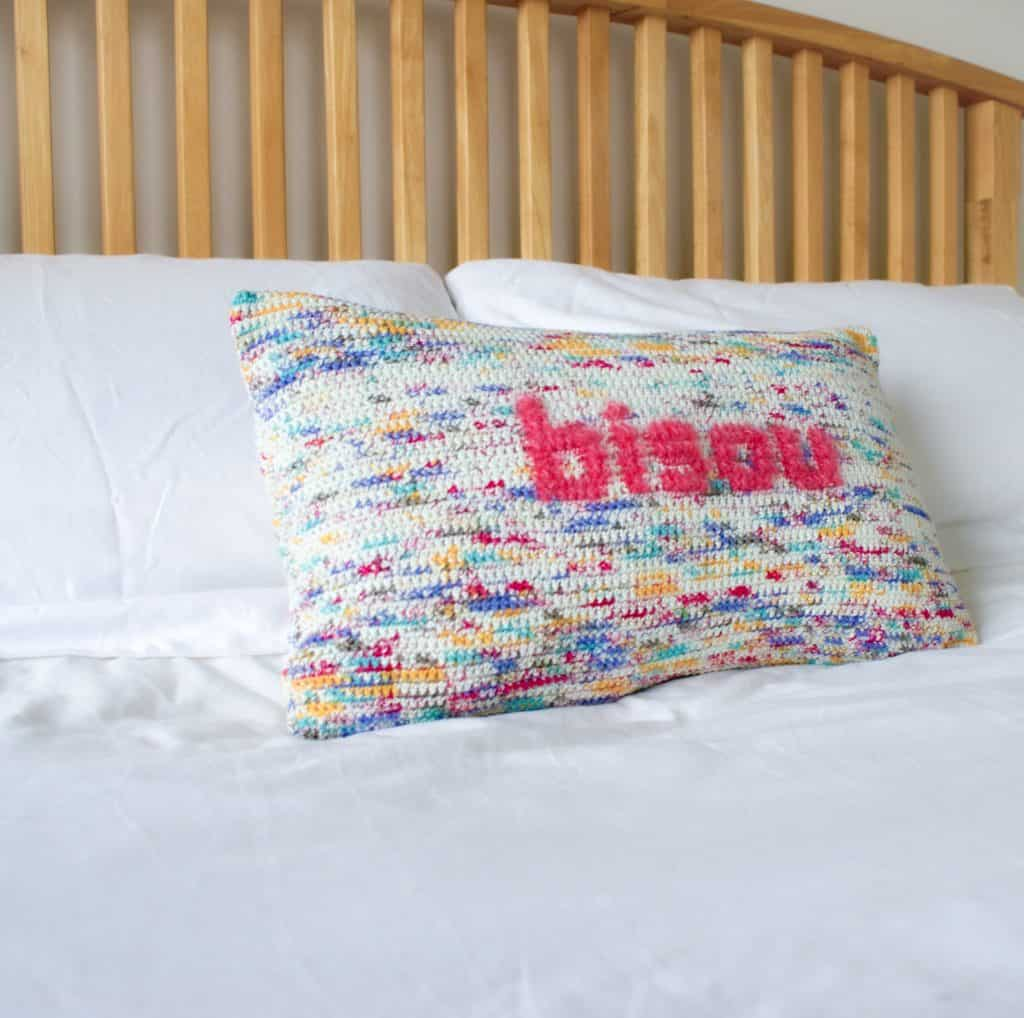 Multi colour crochet pillow with pink fluffy lettering reading bisou sits on a bed with white linen