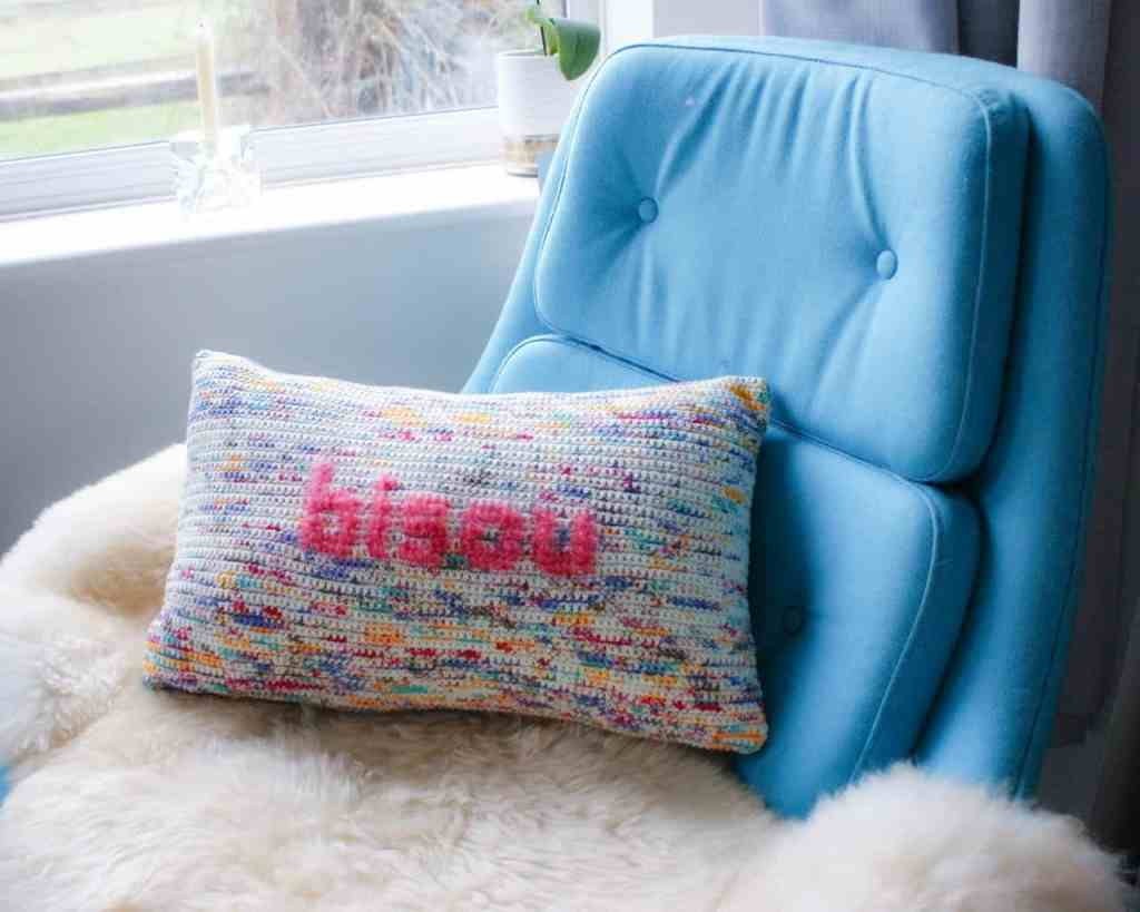 Crochet pillow reading bisou sits on a sheep pelt on a turquoise 50s lounge chair