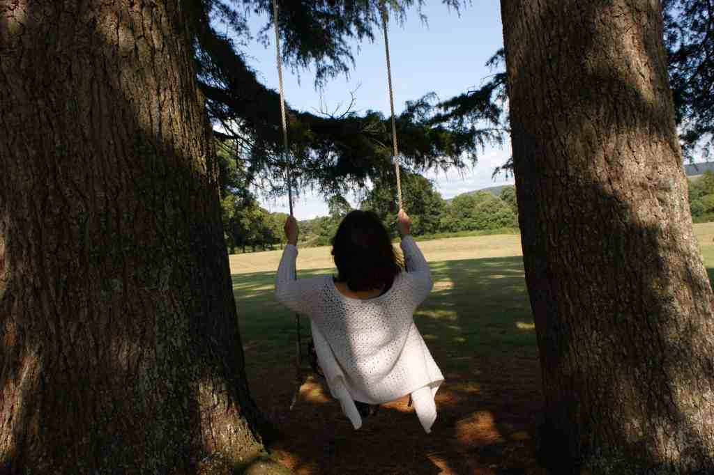Woman in crochet cardigan on swing hung between two trees