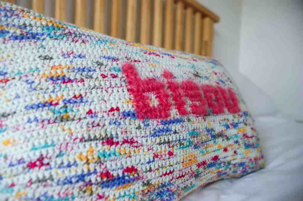 Close up of pink lettering reading bisou on multi coloured crochet pillow