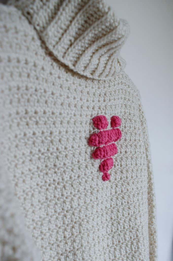 Close up of a pink crochet bobble heart motif on a cream crochet roll neck sweater