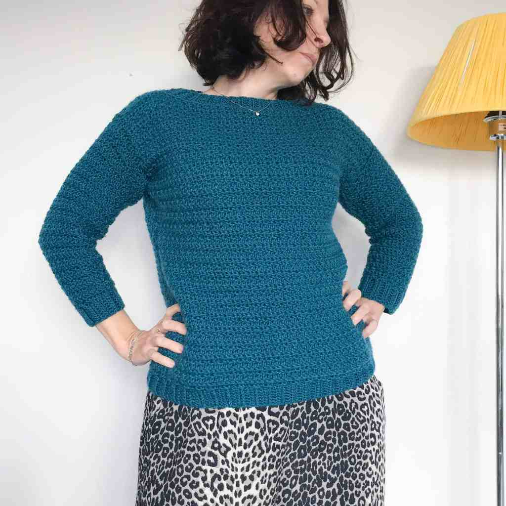 Teal round neck crochet sweater being worn by woman in leopard print trousers