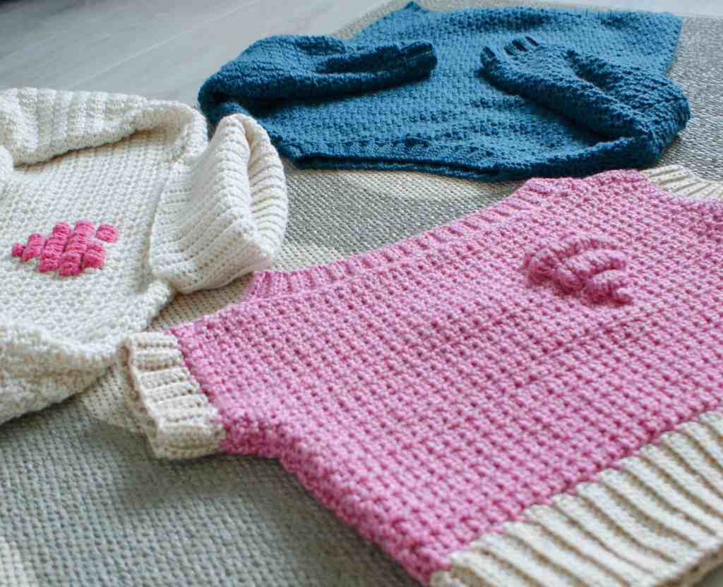 3 crochet sweaters in cream teal and pink, two with pink heart motifs laying on a grey floor