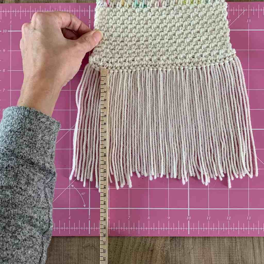 A scarf fringe layin on a pink cutting mat with a ruler measuring the length of fringe