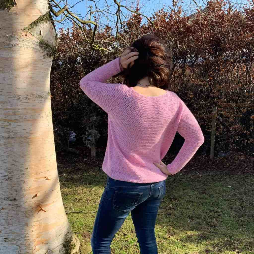 A woman with her back to the camera wearing a pink crochet sweater and blue jeans. One hand in her hair as the wind blows it about