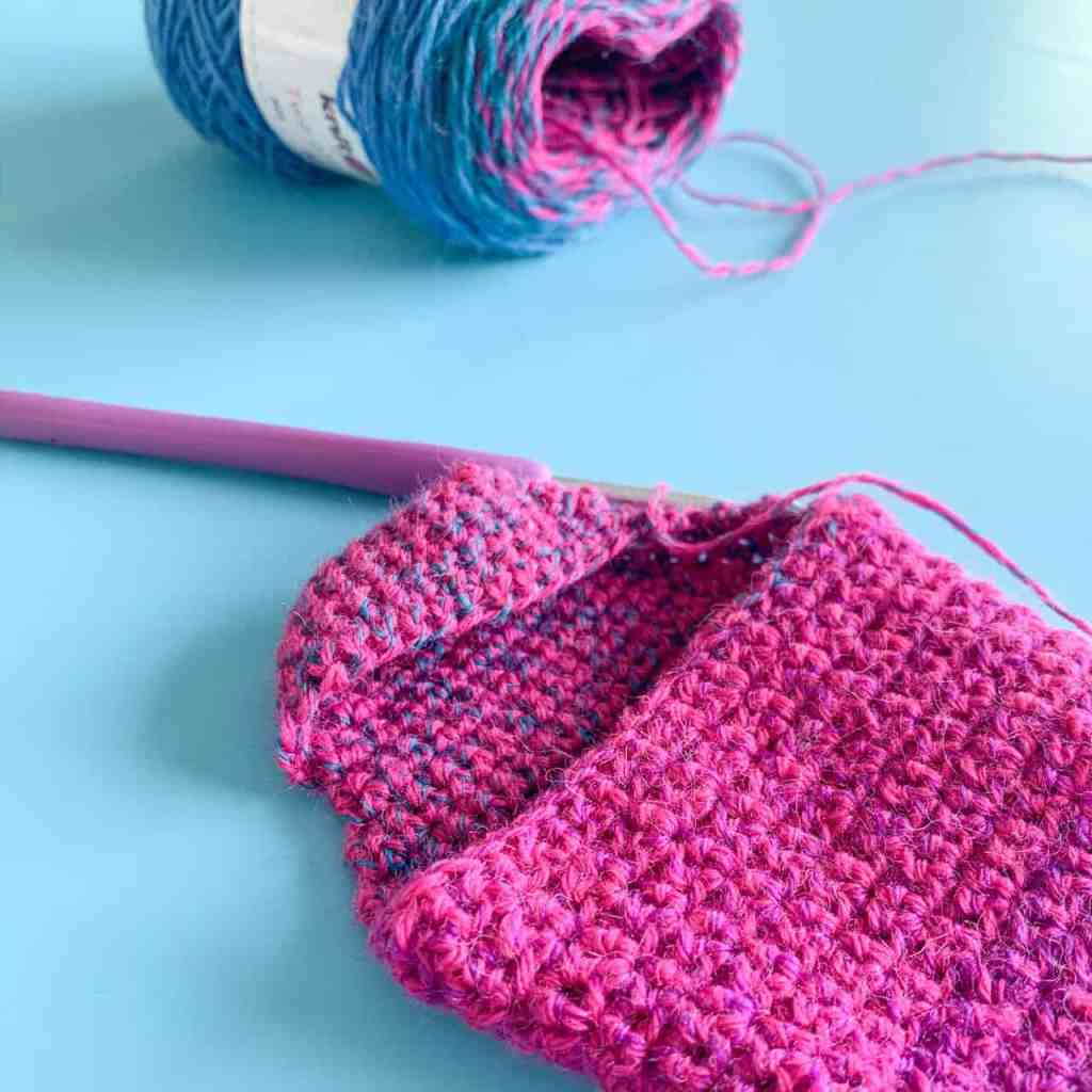Partially made pink crochet sock on blue background