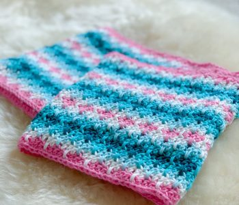 Pink, White Blue and Turquoise stripe crochet infinity scarf folded on a sheepskin rug