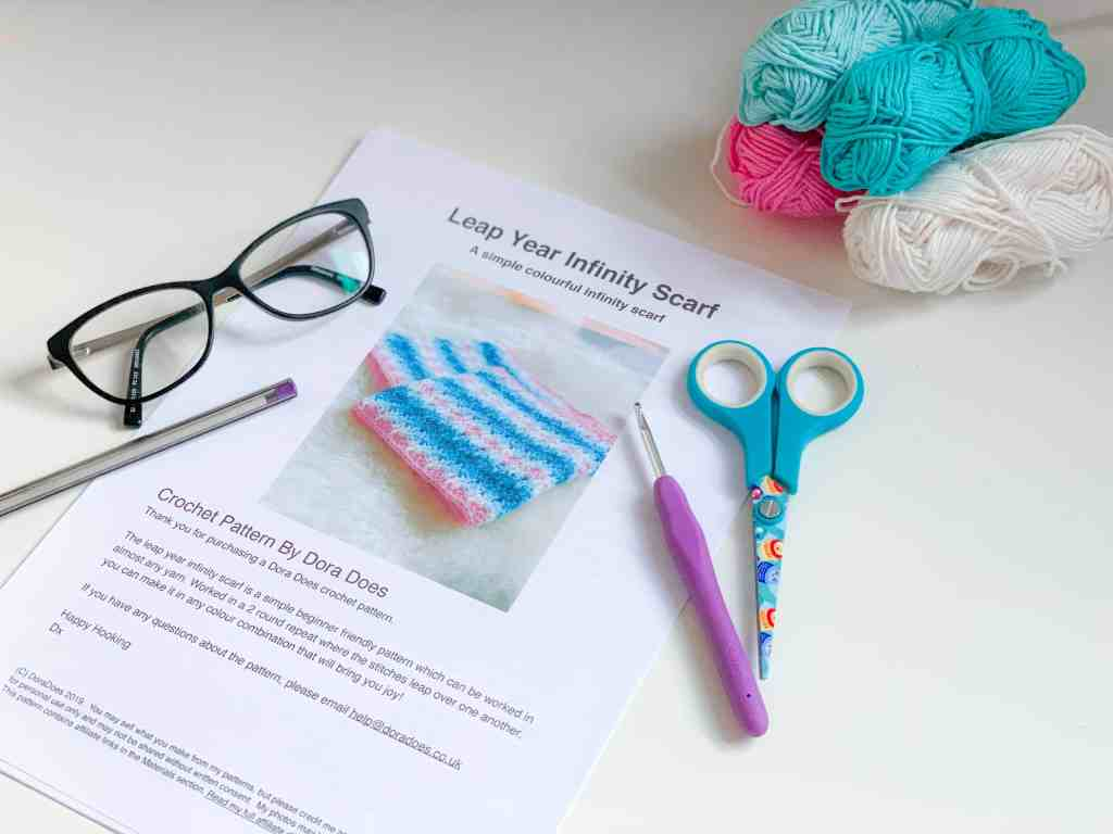 a picture of a desk with a crochet pattern, crochet hook, scissors, yarn, glasses and a pen laid out ready to work