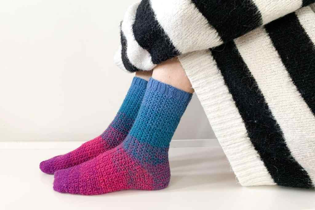 The vibrant pink and blue crochet sock clad feet of a woman sitting on a white surface with a black and white sweater dress pulled down to her shins