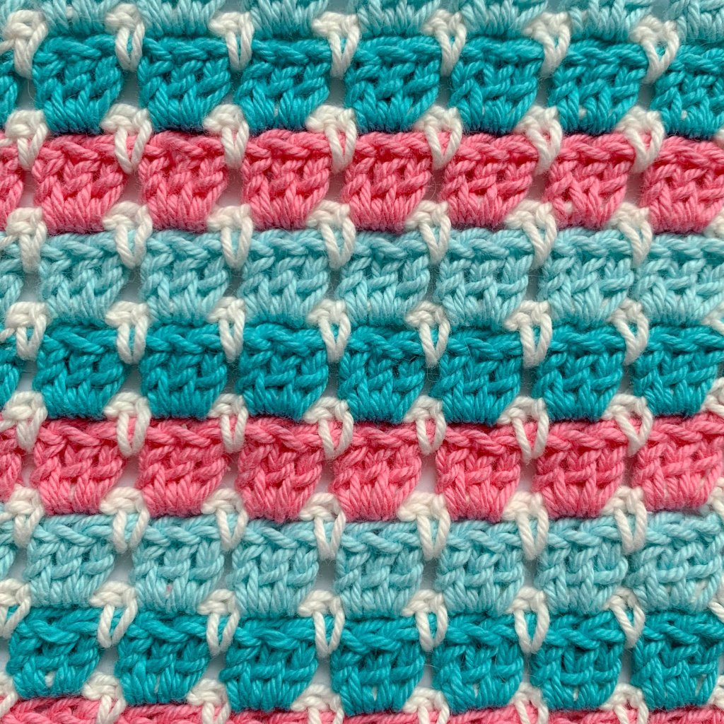 Close up of block stitch pink Aqua, turquoise and white crochet swatch