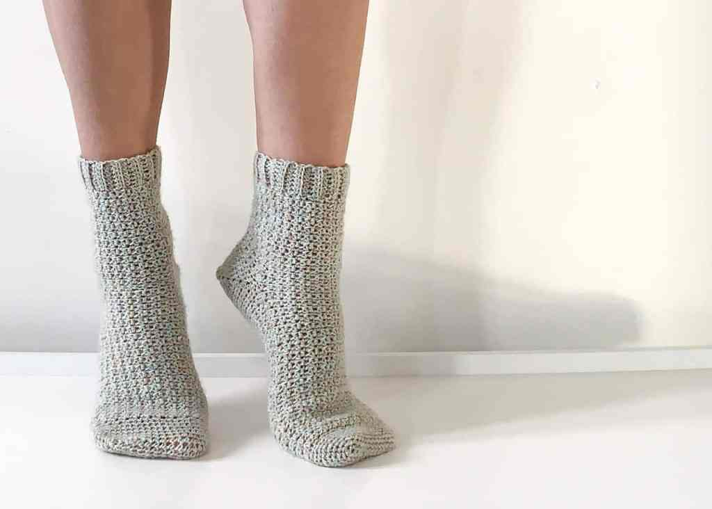 Khaki colour mix crochet socks being modelled by woman standing on white surface