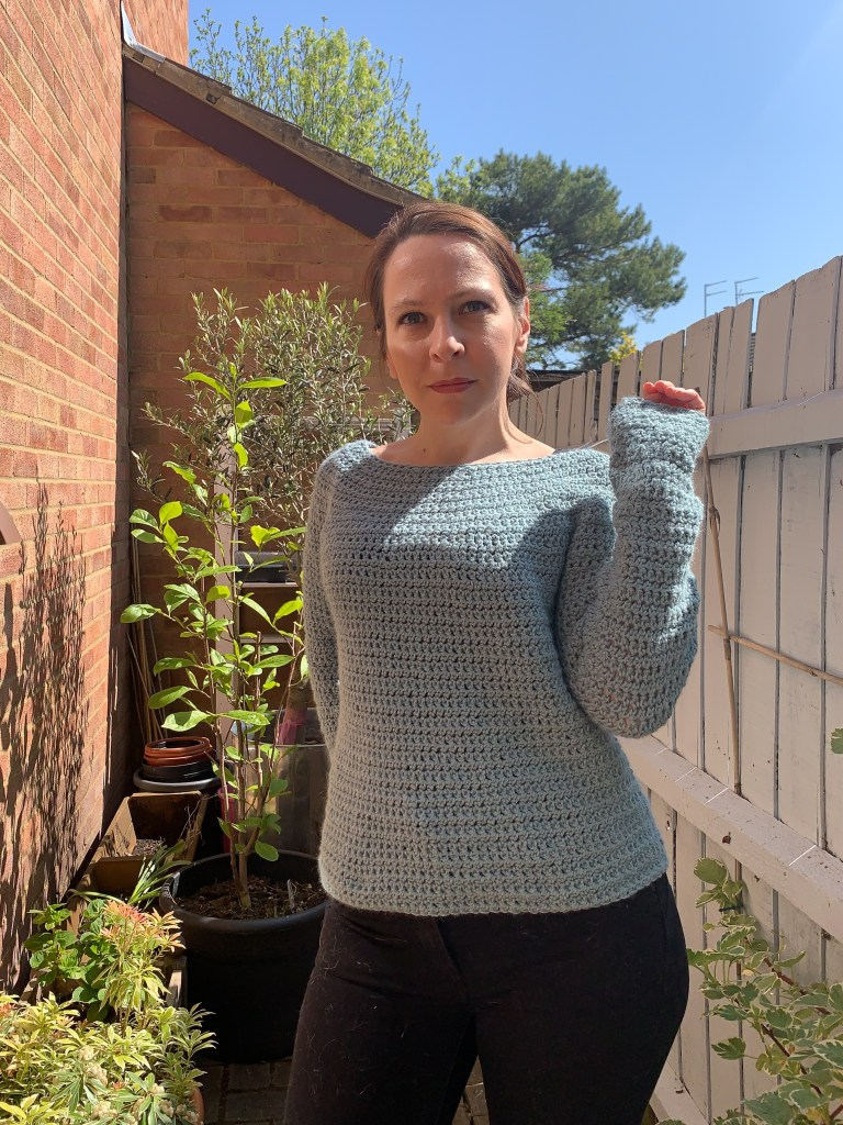 A woman models a Light blue teal crochet sweater in front of a walled garden