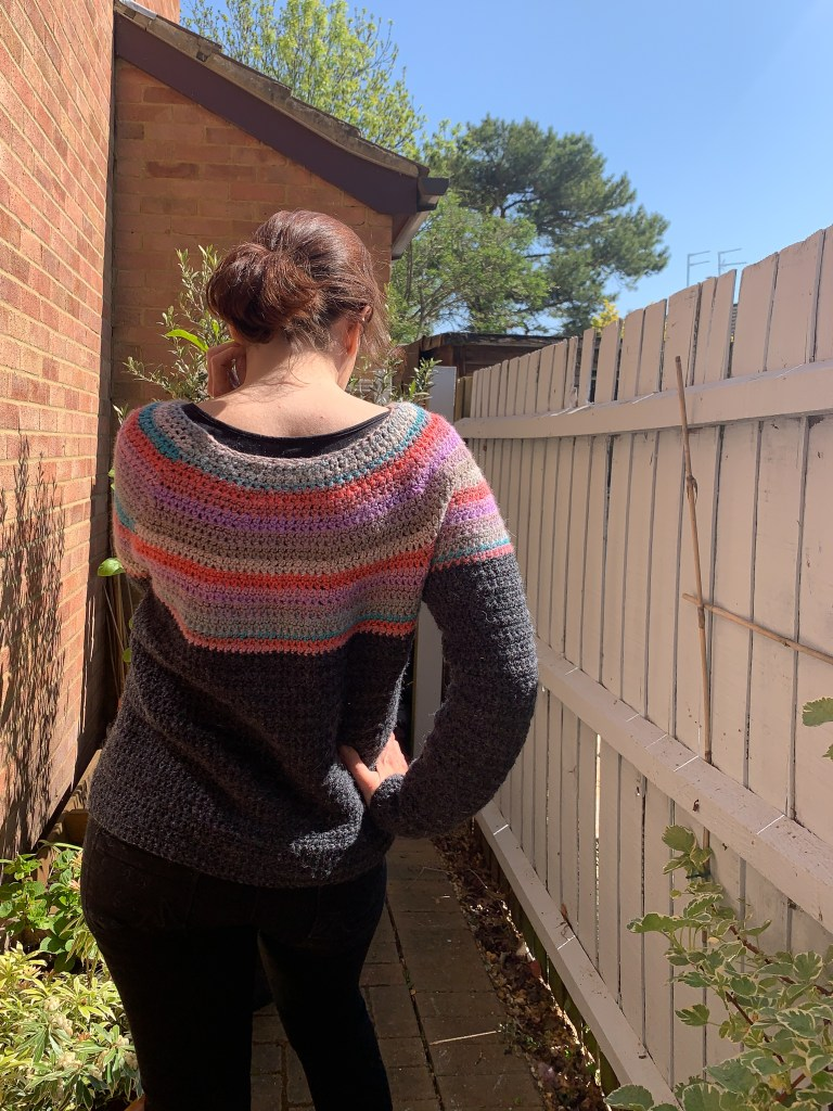 Woman with back to the camera modelling a DK crochet sweater with a colourful yoke and dark grey body