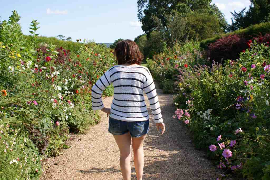 A woman wearing a white crochet sweater with black stripes and denim shorts walks away from the camera through a formal garden