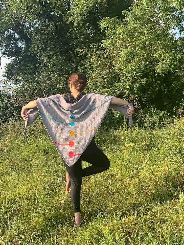 A woman stands with her back to the camera on a meadow holding out a chakra inspired crochet shawl, she is in the standing pigeon yoga pose
