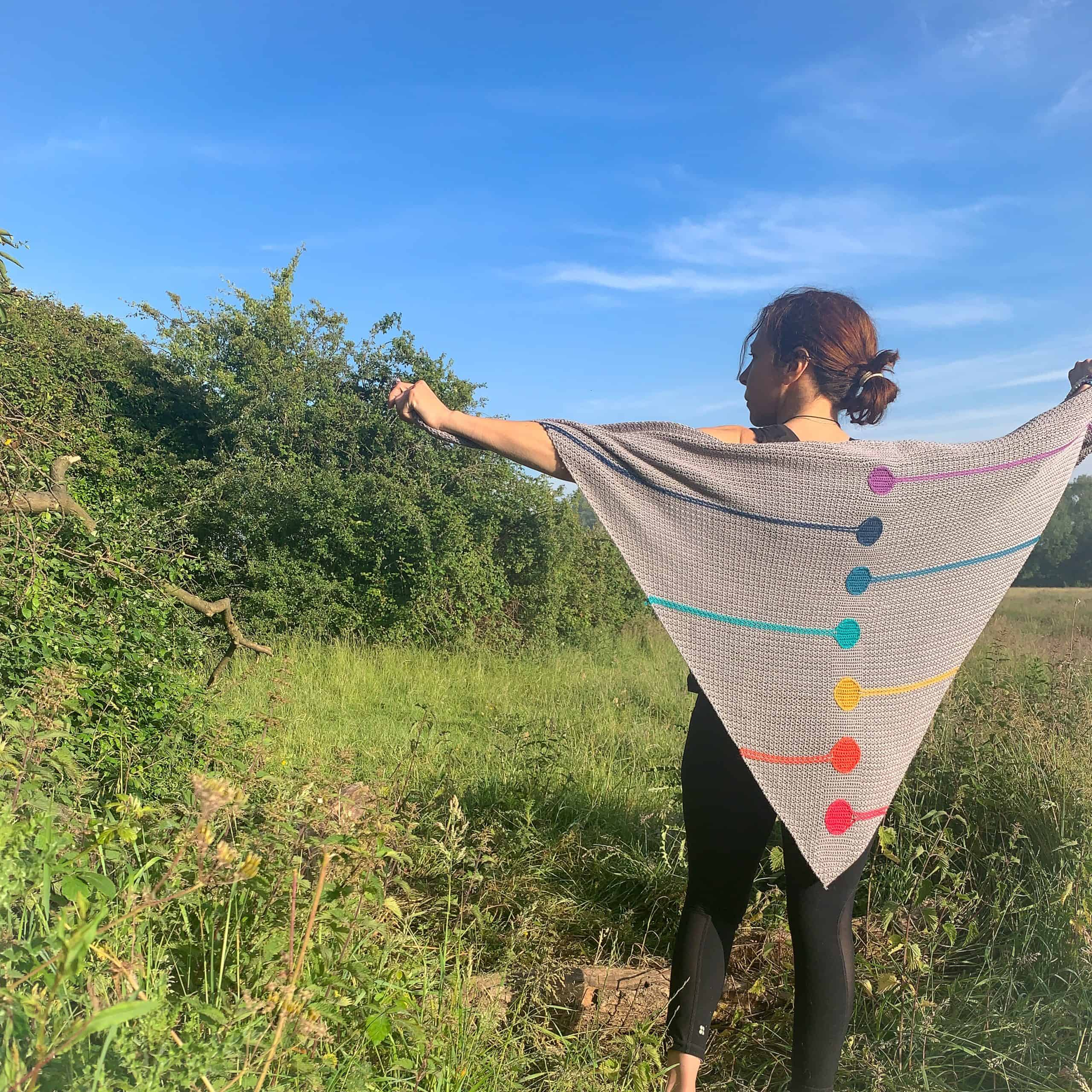 A woman stands with her back to the camera on a meadow holding out a chakra inspired crochet shawl