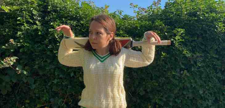 A woman wears a crochet cricket sweater in cream with green stripes, paired with wide leg jeans. She rests her arms on a cricket bat on her shoulder as she stands in front of a hedgerow