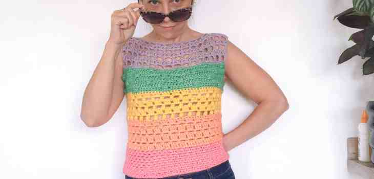 a woman in a bright crochet top and denim short stands in front of a white wall looking at the camera over her sunglasses