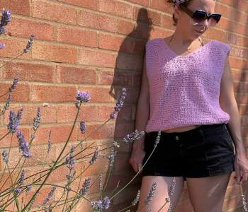 A woman leaning against a brick wall wearing black shorts and a pink crochet vest holds a sprig of lavender in one hand picked from the bush in front of her