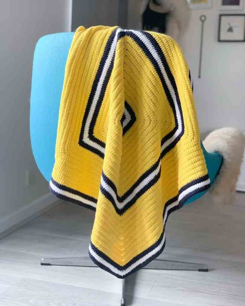 A yellow textured crochet blanket with white and navy stripes is hanging off the back of a turquoise chair in light room
