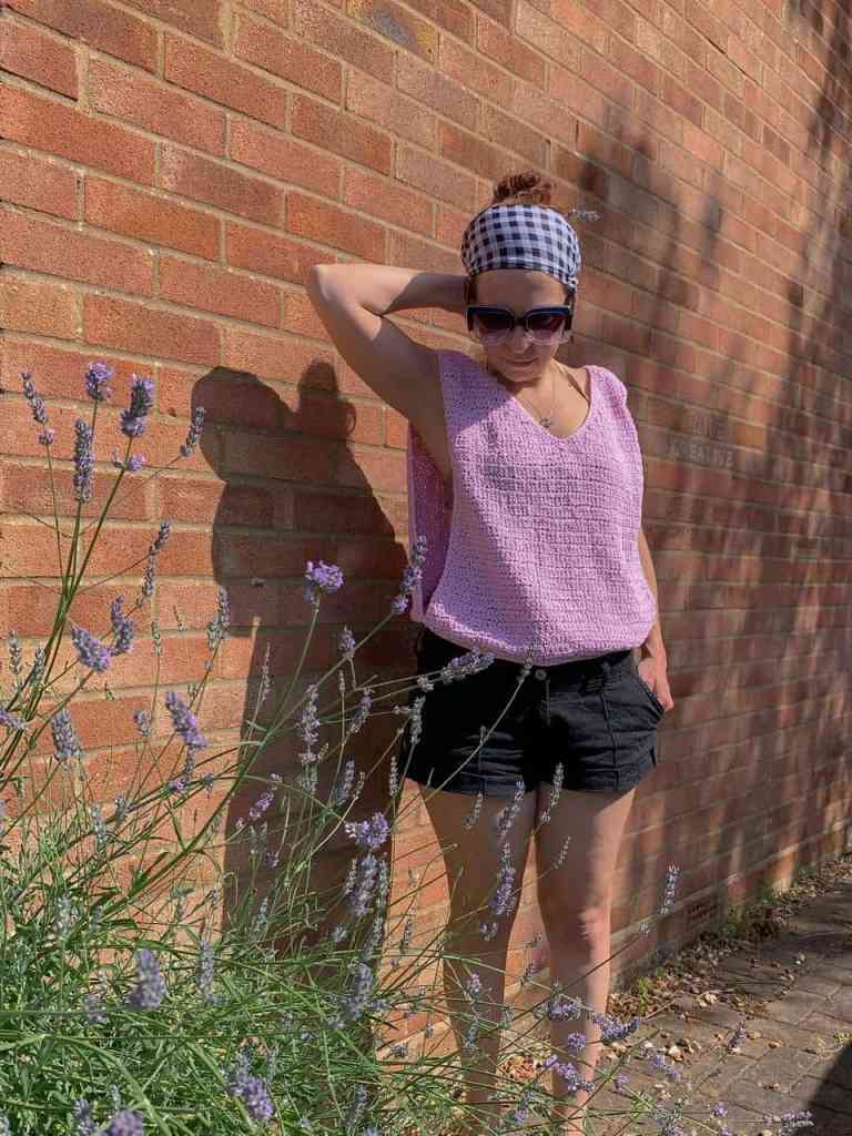 A woman wearing a pink crochet top and black shorts raises her hand to the back of her head as she looks down at the lavender bush in front of her