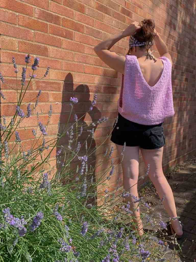 A woman with her back to the camera faces a brick wall, wearing a pink oversized crochet vest and black shorts as she stands half in the sun she tries to put some Lavendar in her hair from the bush she stands behind