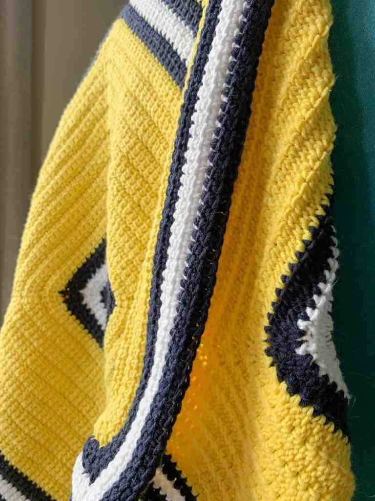 A close up of a yellow textured crochet blanket with white and navy stripes hanging off the back of a chair