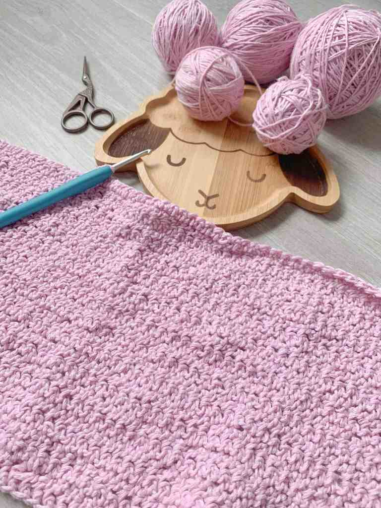 pink crochet fabric representing half a panel is laid on a grey wood floor. A wooden sheep face plate containing balls of yarn lays ned to the fabric which still has a crochet hook attached. A pair of scissors lay to the side.