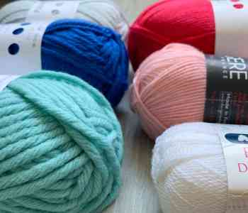 An angled close up of 6 different weight, different coloured balls of yarn