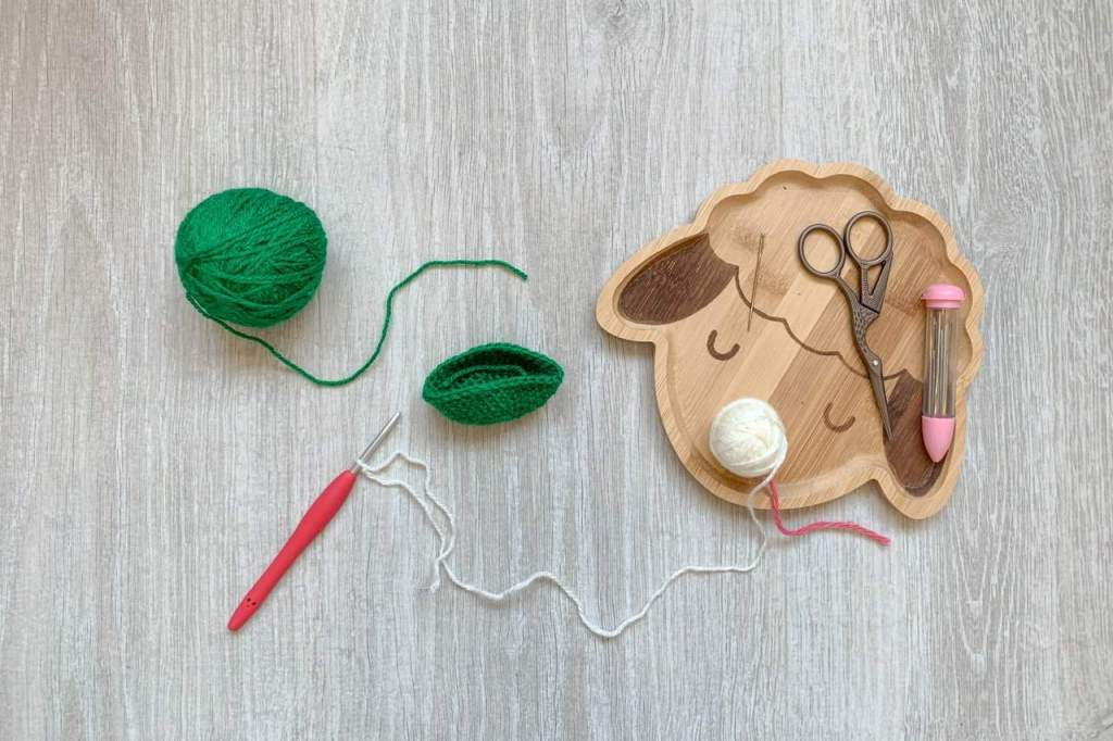 A small green part worked crochet project lays on the floor with a green ball of yarn, a cream ball of yarn and a red crochet hook