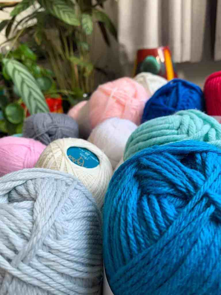 A close up of ble and grey yarn with other balls bundled behind with a plant and red pots in the background blurred out